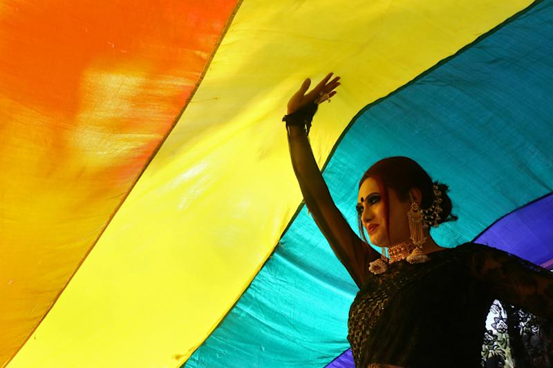 A participant walks under a rainbow flag during a pride parade in 2018. (Image: REUTERS)