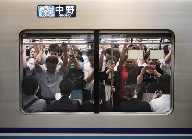 In this July 31, 2019, photo, commuters are seen through the window of an overcrowded train during morning rush hours at Kiba Station in Tokyo. Tokyo has one of the most advanced public transport systems in the world, but with less than one year to go before the city hosts the 2020 Olympic Games, local governments, companies and commuters are bracing for unprecedented strain the events could put on rail transit and highways. (AP Photo/Jae C. Hong)