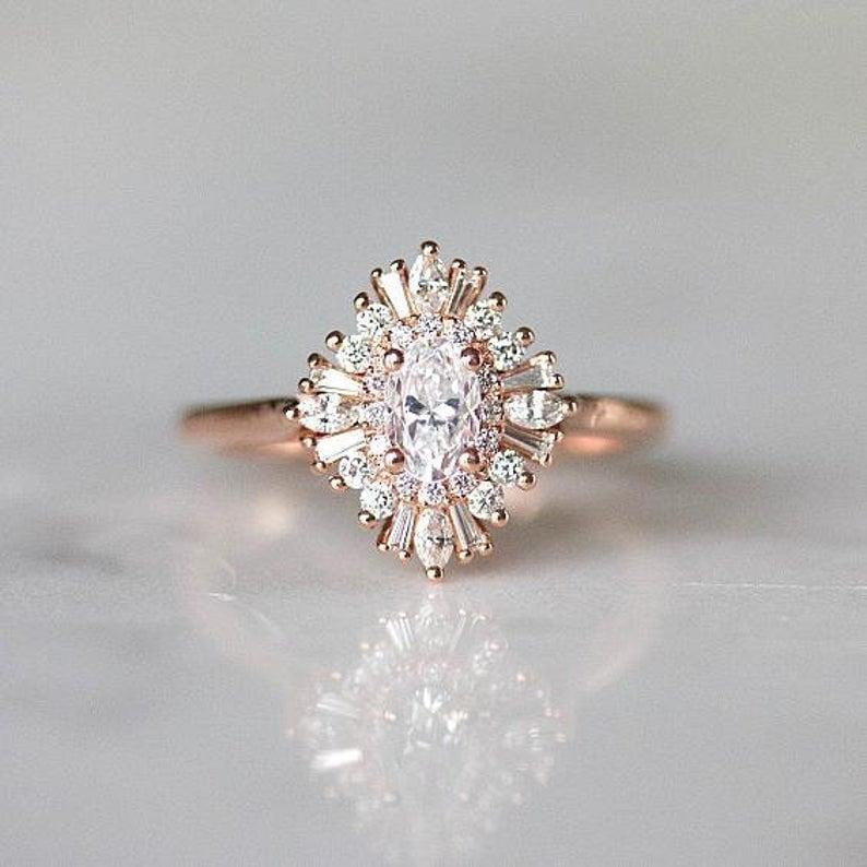 """<p>This '20s-inspired <a href=""""https://www.popsugar.com/buy/Gatsby-Style-Engagement-Ring-531230?p_name=Gatsby%20Style%20Engagement%20Ring&retailer=etsy.com&pid=531230&price=2%2C102&evar1=fab%3Aus&evar9=7954958&evar98=https%3A%2F%2Fwww.popsugar.com%2Fphoto-gallery%2F7954958%2Fimage%2F47020630%2FGatsby-Style-Engagement-Ring&list1=shopping%2Cwedding%2Cjewelry%2Crings%2Cbride%2Cengagement%20rings%2Cfashion%20shopping&prop13=api&pdata=1"""" rel=""""nofollow noopener"""" class=""""link rapid-noclick-resp"""" target=""""_blank"""" data-ylk=""""slk:Gatsby Style Engagement Ring"""">Gatsby Style Engagement Ring </a> ($2,102) features petite diamonds and a moissanite centre stone.</p>"""
