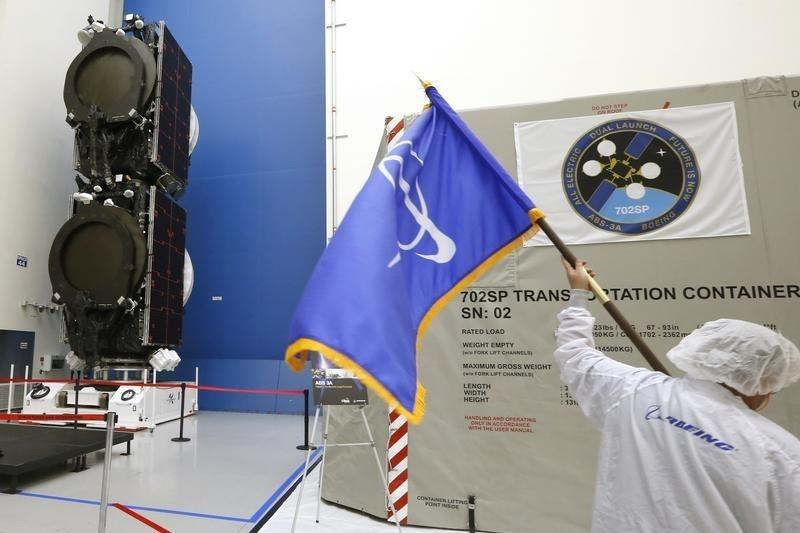 A man carries a flag with the Boeing logo past the world's first two all-electric propulsion 702SP satellites in the Boeing Satellite Development Center in El Segundo