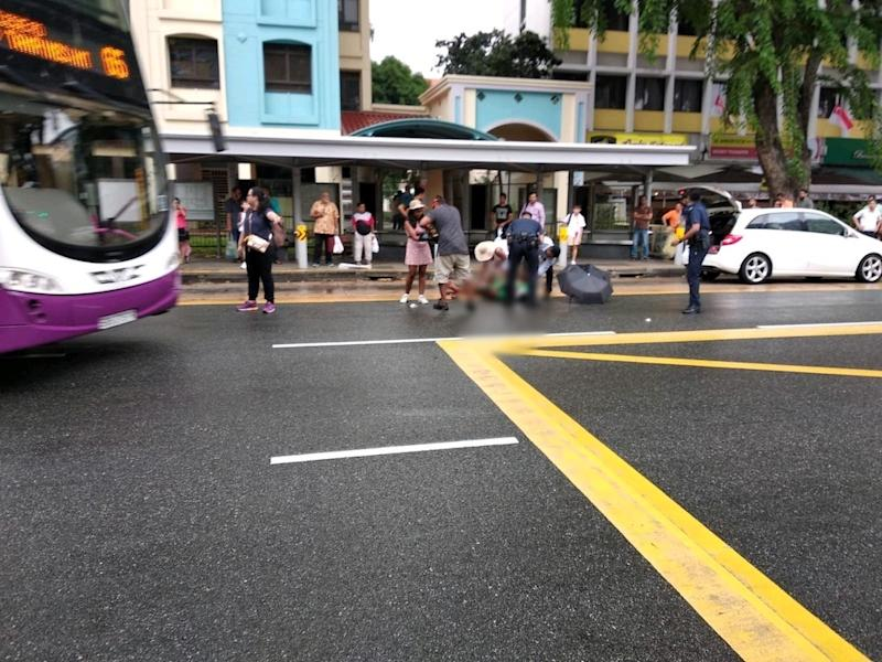 Policemen and passers-by attending to the victim after the assault. (Photo: Facebook page of KP Lau)