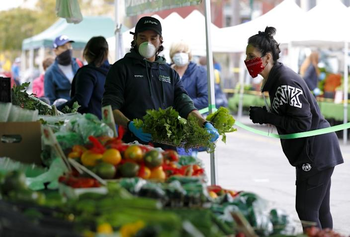 At the Farmers Market in Little Italy on Saturday, April 4, 2020, Stephen Clark from JR Organics helped Lori Vanderlinden select fresh produce while standing behind the tape. Grocery vendors are required to wear a face mask and customers could no longer hand select the produce for themselves.