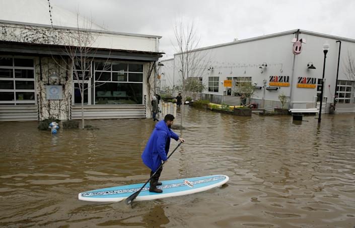 A man uses a paddle board to make his way through the flooded Barlow Market District Wednesday, February 27, 2019, in Sebastopol, California.