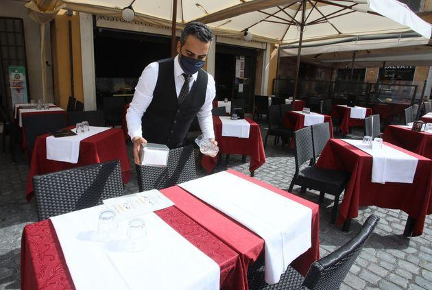 ROME, ITALY - APRIL 29,2021: A waiter sets a table in an open space of a restaurant in Rome, because from Monday 26 April Italy will gradually reopen after six months of rolling virus blocks. (Photo credit should read Marco Ravagli/Barcroft Media via Getty Images) (Photo: Barcroft Media via Barcroft Media via Getty Images)