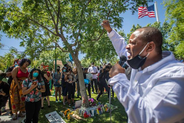 People gather around a makeshift memorial at the tree where Robert Fuller was found hanging in Palmdale, Calif. (Apu Gomes/AFP via Getty Images)