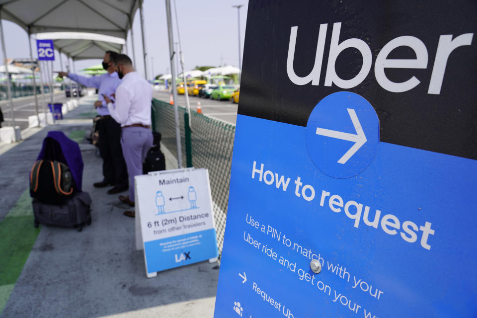FILE - In this Aug. 20, 2020 file photo, travelers request an Uber ride at Los Angeles International Airport's LAX-it pick up terminal. Drivers for app-based ride-hailing and delivery services are suing to overturn a California ballot initiative that makes them independent contractors instead of employees eligible for benefits and job protections. The lawsuit filed Tuesday, Jan. 12, 2021 in the California Supreme Court said Proposition 22 is unconstitutional because it limits the power of the Legislature to grant workers the right to organize and excludes drivers from being eligible for workers' compensation. (AP Photo/Damian Dovarganes, File)