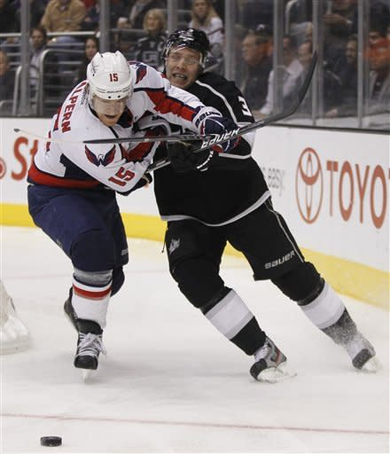 Washington Capitals center Jeff Halpern, left, battles Los Angeles Kings defenseman Jack Johnson for the puck during the first period of an NHL hockey game in Los Angeles, Monday, Jan. 9, 2012. (AP Photo/Chris Carlson)