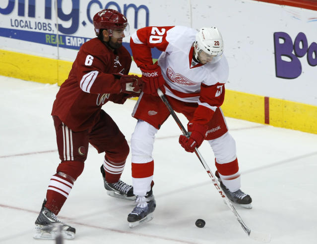 Phoenix Coyotes defenseman David Schlemko (6) tries to slow Detroit Red Wings left wing Drew Miller (20) in the second period of an NHL hockey game Saturday, Oct. 19, 2013, in Glendale, Ariz. (AP Photo/Rick Scuteri)