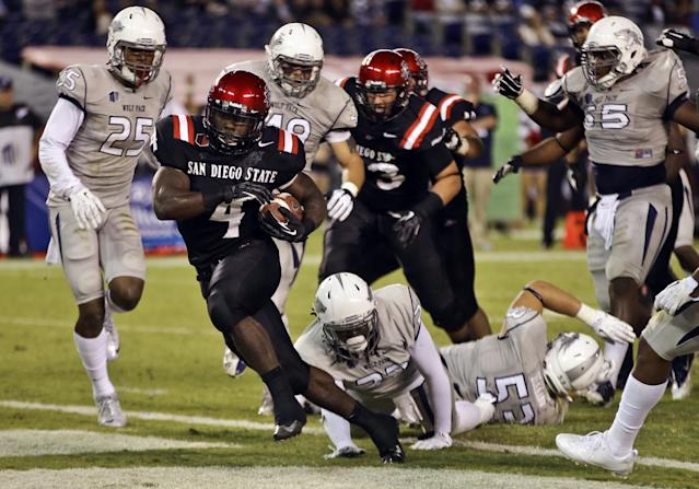 San Diego State running back Adam Muema (4) breaks through the Nevada defense to score on a 7-yard run during the second quarter of an NCAA college football game on Friday, Oct. 4, 2013, in San Diego. (AP Photo/Lenny Ignelzi)