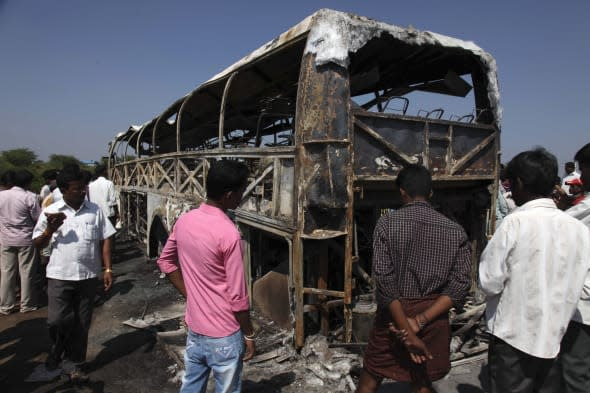 India Bus Inferno (People gather near the debris of a bus after it crashed into a highway barrier and erupted in flames at Mehab