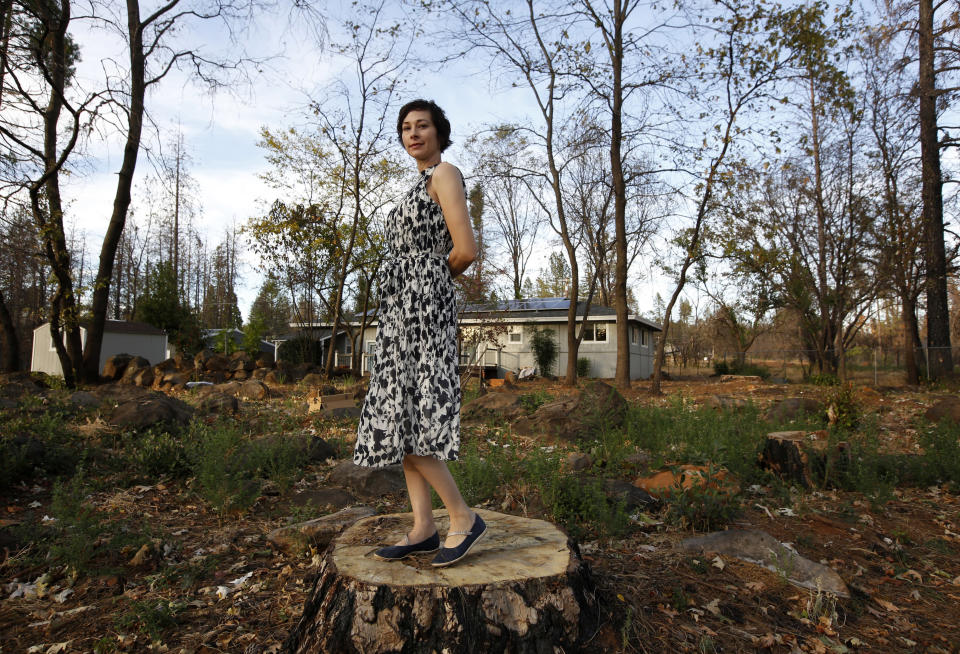 In this Thursday, Oct. 24, 2019, photo, Libby Hail poses at her home that was not destroyed when last year's Camp Fire destroyed nearly 9,000 homes when it swept through Paradise, Calif. Hail's home survived due to a wide skirt of gravel and its fire-resistant stucco construction. The Hails also paid to have numerous large, fire-damaged trees removed from their backyard after the fire. (AP Photo/Rich Pedroncelli)