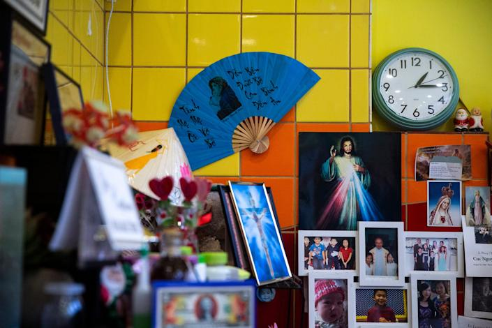 "Brenda Tran displays her ""angels"" — photos and funeral programs of departed friends and customers with a big photo of her father in the center at Vietnam Cafe."