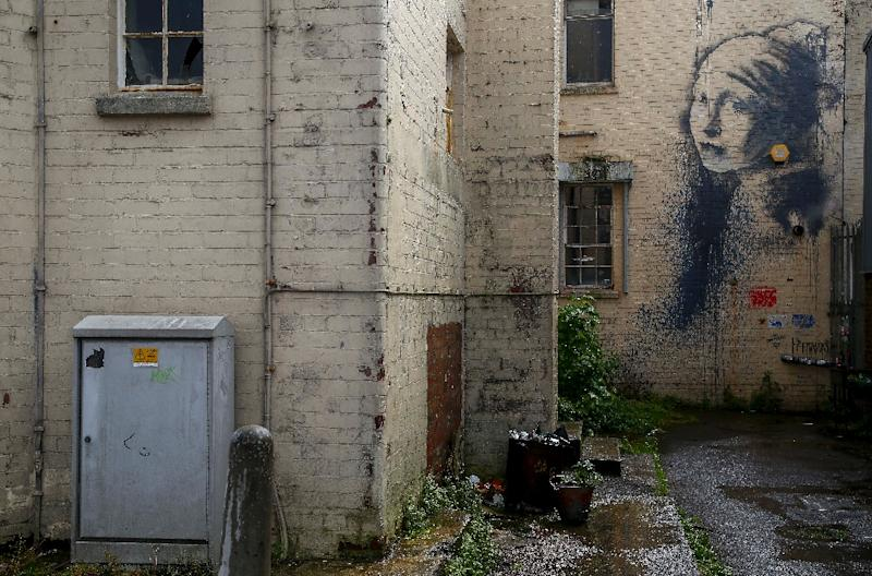 "Like many other spots the mysterious artist has decorated in his purported home city of Bristol, the courtyard beneath his ""The Girl with a Pierced Eardrum"" is one of Britain's most photographed places (AFP Photo/GEOFF CADDICK)"