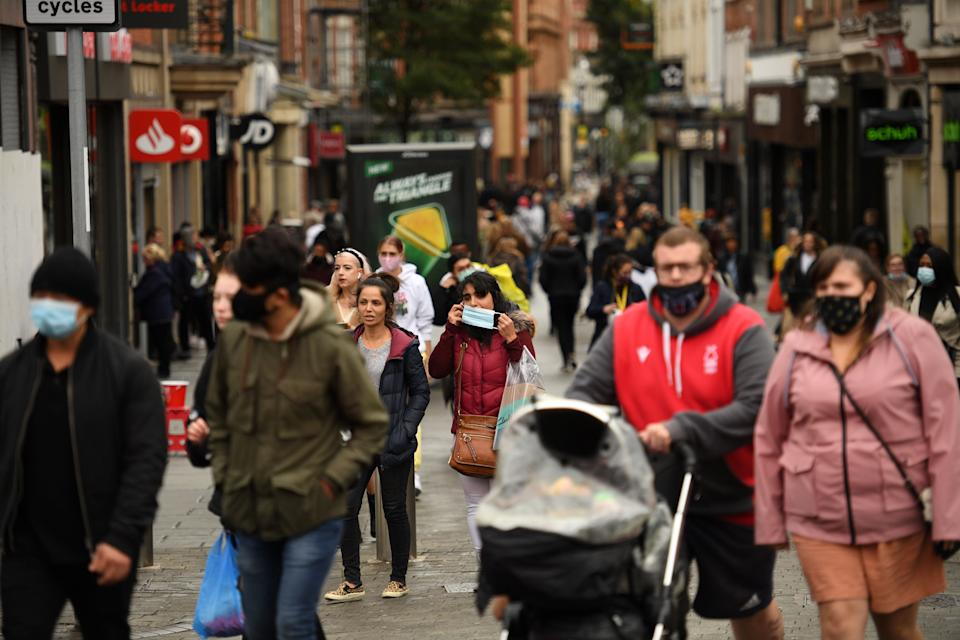 "Pedestrians, many wearing protective face coverings to combat the spread of coronavirus covid-19 walk through central Nottingham in central England on October 9, 2020. - Pubs and restaurants in coronavirus hotspots look set to face fresh restrictions after Downing Street said new data suggests there is ""significant"" transmission taking place in hospitality settings. A ""range of measures"" is being looked at, with a particular focus on northern England, where it says infection rates are rising fastest. (Photo by Oli SCARFF / AFP) (Photo by OLI SCARFF/AFP via Getty Images)"