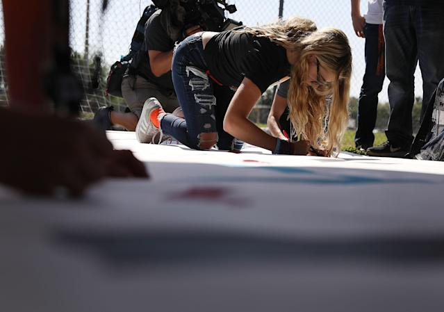 <p>Delany Tarr, a senior, signs a poster as she gathers together with some of her fellow students from Marjory Stoneman Douglas High School, where 17 classmates and teachers were killed during a mass shooting, after walking out of school during the National School Walkout on April 20, 2018 in Parkland, Fla. (Photo: Joe Raedle/Getty Images) </p>