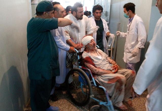 <p>Relatives assist a wounded man in a hospital after a suicide attack on a mosque in Herat, Afghanistan, Tuesday, Aug. 1, 2017. (Photo: Hamed Sarfarazi/AP) </p>
