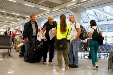 Passengers are seen at Thomas Cook check-in points at Mallorca Airport as an announcement is expected on the tour operator, in Palma de Mallorca