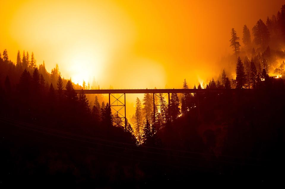 The Dixie Fire burns behind a bridge in Plumas County, Calif., on July 25.