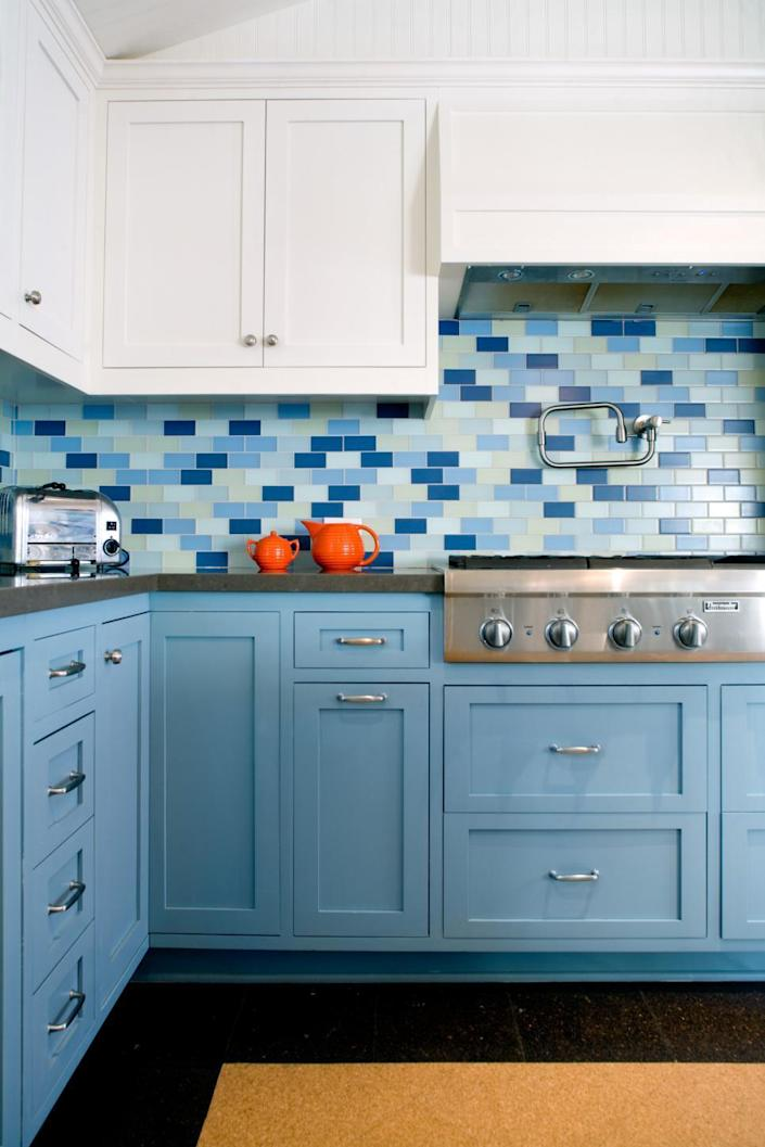 <p>But why stick to just one color when you can give your kitchen a totally unexpected look simply by mixing variant hues of the same color? In this transitional kitchen, blue tiles with different levels of saturation are tied together by white upper cabinets and solid blue lower cabinets. <i>Design by Jeff Troyer Associates; photo by Lee Manning.</i></p>