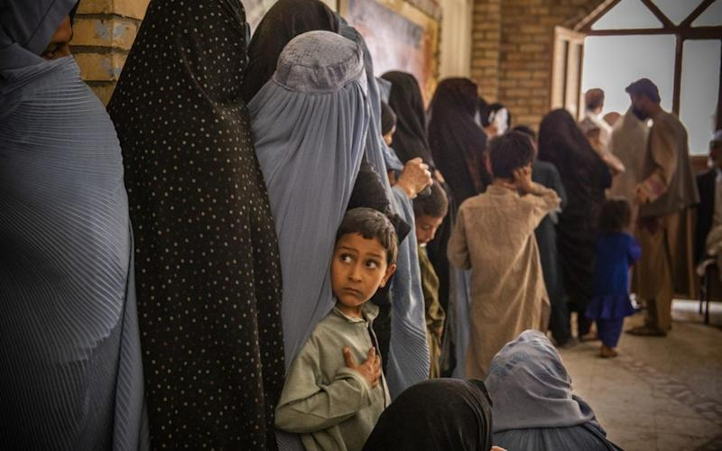 A young boy waits in line with his mother at a food distribution in Afghanistan organised by Oxfam - Kiana Hayeri/Oxfam