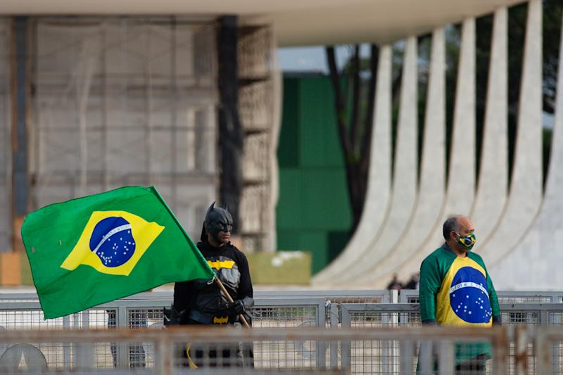 BRASILIA, BRAZIL - MAY 15: Supporters of Brazilian President Jair Bolsonaro wearing a Batman costume and holding a flag await his appearance on the ramp of the Planalto Palace amidst the coronavirus (COVID-19) pandemic in front the Planalto Palace on May 15, 2020 in Brasilia. Brazil has over 202,000 confirmed positive cases of Coronavirus and 13,993 deaths. (Photo by Andressa Anholete/Getty Images)