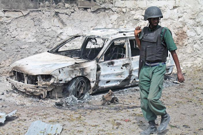 A Somali soldier walks near a destroyed car near the entrance of Mogadishu's court complex, Mogadishu, Somalia, Sunday, April 14, 2013. Militants launched a serious and sustained assault on Mogadishu's main court complex Sunday, detonating at least two blasts, taking an unknown number of hostages and exchanging extended volleys of gunfire with government security forces, witnesses said.(AP Photo/Farah Abdi Warsameh)