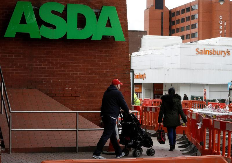 People walk past branches of ASDA and Sainsbury's in Stockport.