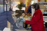 A cashier wears a sanitary mask as she talks to a client in a supermarket in Casalpusterlengo, Northern Italy, Monday, Feb. 24, 2020. Italy scrambled to check the spread of Europe's first major outbreak of the new viral disease amid rapidly rising numbers of infections and a third death. Road blocks were set up in at least some of 10 towns in Lombardy at the epicenter of the outbreak, including in Casalpusterlengo, to keep people from leaving or arriving. (AP Photo/Paolo Santalucia)