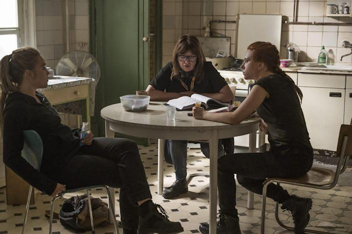 Scarlett Johanson, Florence Pugh, Cate Shortland in Black Widow sit around a table in a behind the scenes image