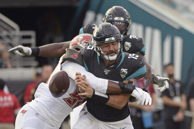 Tampa Bay Buccaneers linebacker Sam Acho, left, forces a fumble as he sacks Jacksonville Jaguars quarterback Gardner Minshew (15) during the second half of an NFL football game, Sunday, Dec. 1, 2019, in Jacksonville, Fla. (AP Photo/Phelan M. Ebenhack)