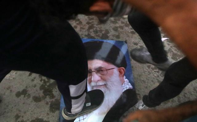 <p>Protesters trample a portrait of Iran's supreme Leader Ayatollah Ali Khamenei, during the storming and burning the Iranian consulate in Basra, 340 miles (550 km) southeast of Baghdad, Iraq, Friday, Sept. 7, 2018. (Photo: Nabil al-Jurani/AP) </p>