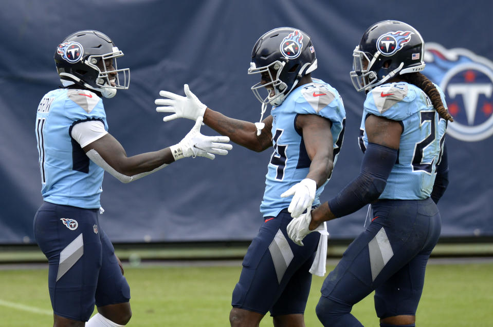 FILE - In this Oct. 25, 2020, file photo, Tennessee Titans wide receiver A.J. Brown (11) is congratulated by Corey Davis (84) and Derrick Henry (22) after Brown scored a touchdown on a 73-yard pass reception in the second half of an NFL football game against the Pittsburgh Steelers in Nashville, Tenn. Tennessee has been looking for years for top wide receivers, and the Titans now have two in A.J. Brown and Corey Davis who make big plays with key catches while also blocking for Henry whenever the NFL's leading rusher has the ball. (AP Photo/Mark Zaleski, File)