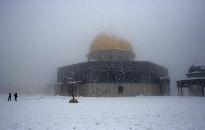 Palestinian children play in the snow in front of the Dome of the Rock mosque in the old city of Jerusalem on February 20, 2015 (AFP Photo/Ahmad Gharabli)