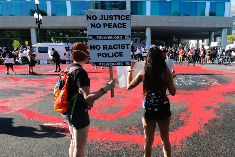 In this July 9, 2020, file photo, protesters gather in front of district attorney's office in Salt Lake City, where demonstrators covered the street in red paint