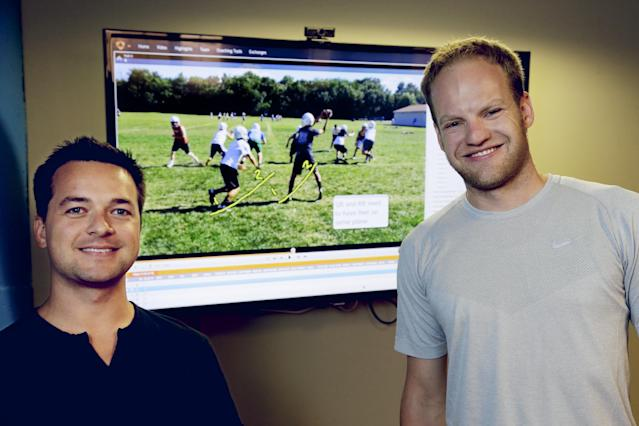 In this photo from Aug. 14, 2014, David Graff, CEO of Hudl, right, and John Wirtz, Chief Product Officer, pose for a photo in front of a screen showing their company's product, in Lincoln, Neb. Hudl is a software company that has developed a way to immediately get game film to coaches after games and break down and separate different plays by type. (AP Photo/Nati Harnik)