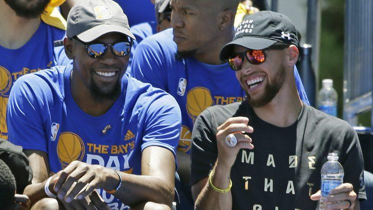 Kevin Durant and Stephen Curry find something funny. (AP)