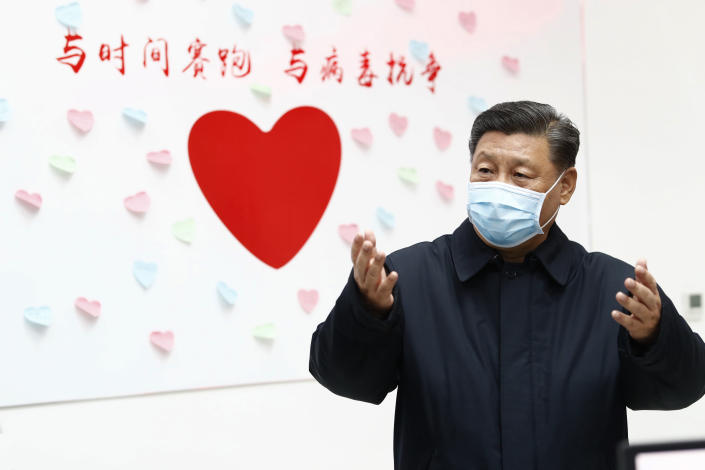 """In this Feb. 10, 2020, photo released by Xinhua News Agency, Chinese President Xi Jinping gestures near a heart shape sign and the slogan """"Race against time, Fight the Virus"""" during an inspection of the center for disease control and prevention of Chaoyang District in Beijing. As the rest of the world grapples with a burgeoning virus outbreak, China's ruling Communist Party has turned to its propaganda playbook to portray its leader as firmly in charge, leading an army of health workers in a """"people's war"""" against the disease. (Liu Bin/Xinhua via AP, File)"""