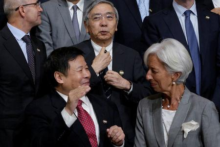 Bank of Japan (BOJ) Governor Haruhiko Kuroda (C) adjusts his tie behind International Monetary Fund (IMF) Managing Director Christine Lagarde (R) and Chinese Vice Finance Minister Zhu Guangyao at G-20 finance ministers and central bank governors family photo before a plenary session during the IMF/World Bank annual meetings in Washington, U.S., October 12, 2017. REUTERS/Yuri Gripas