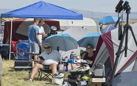 Visitors wait and adjust telescopes Solartown in Madras, Oregon  - Credit: Barcroft Media