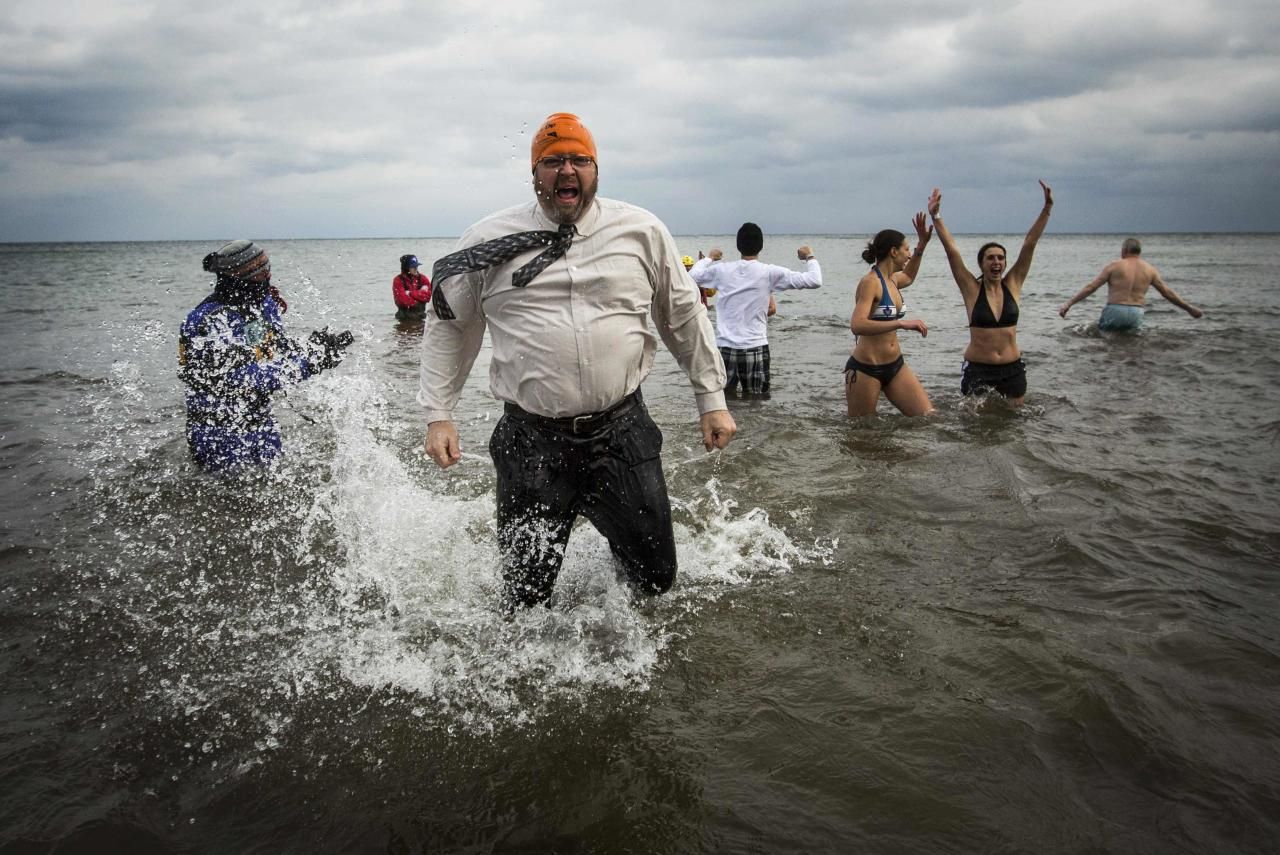 "Participants take part in Courage Polar Bear Dip at Coronation Park in Oakville, January 1, 2015. This year's edition of the Courage Polar Bear Dip, in which hundreds of participants ran into Lake Ontario in subfreezing temperatures, will raise money for the ""Rwanda: Right to Clean Water"" project. REUTERS/Mark Blinch (CANADA - Tags: SOCIETY)"