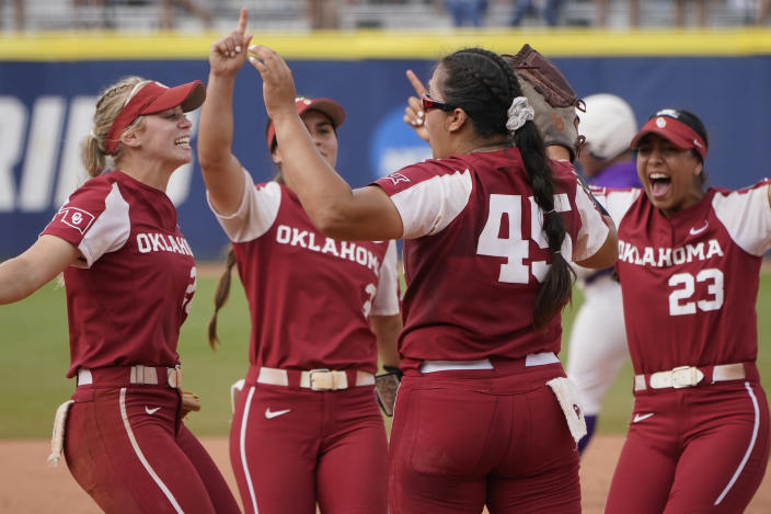 Oklahoma pitcher Giselle Juarez (45) celebrates with teammates after they defeated James Madison in an NCAA Women's College World Series softball game Monday, June 7, 2021, in Oklahoma City. Oklahoma moves onto the championship finals series. (AP Photo/Sue Ogrocki)