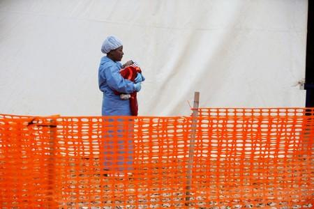 FILE PHOTO: Rachel Kahindo, Ebola survivor working as a caregiver to babies who are confirmed Ebola cases, holds an infant outside the red zone at the Ebola treatment centre in Butembo
