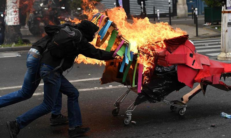 People push a burning trolley towards riot police during march in Paris