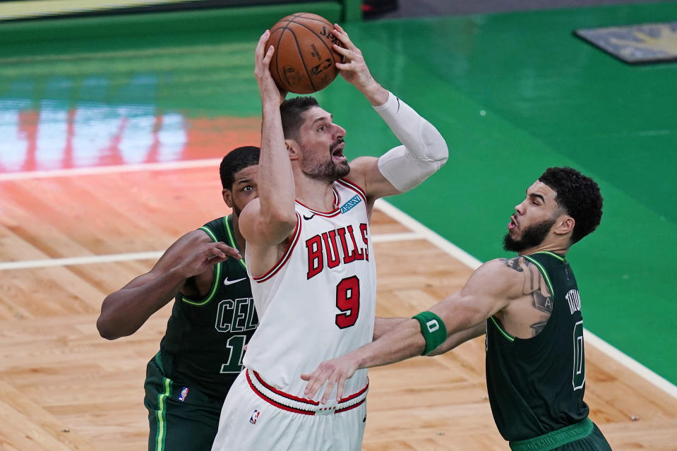 Chicago Bulls center Nikola Vucevic (9) shoots while pressured Boston Celtics forward Jayson Tatum, right, and center Tristan Thompson, rear, during the second half of an NBA basketball game, Monday, April 19, 2021, in Boston. (AP Photo/Charles Krupa)