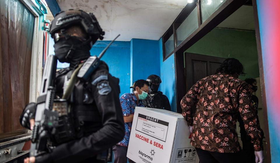 Workers unload Sinovac vaccines from a truck under police escort in Surabaya, Indonesia, on Monday. Photo: AFP
