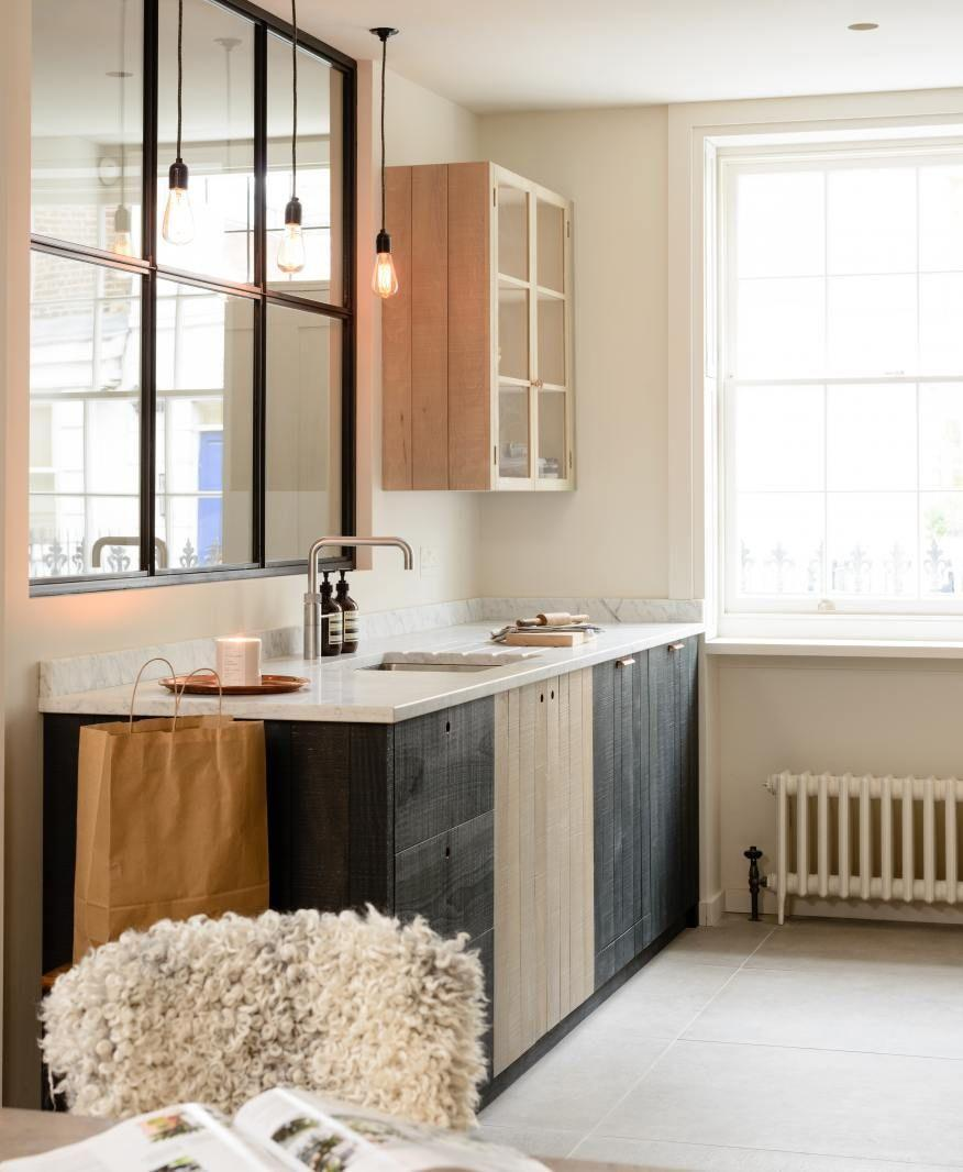 "<p>We're really digging the alternating black and gray stained wood cabinets in this <a href=""https://www.devolkitchens.co.uk/kitchens/shaker-range/brochure"" rel=""nofollow noopener"" target=""_blank"" data-ylk=""slk:deVOL"" class=""link rapid-noclick-resp"">deVOL</a> kitchen. The varied tones (plus texture) adds interest to a neutral space. The sandy beige walls keep things neutral but warms thing a little more than a crisp white or super light gray. The shearling chair cover warms up, too, and the interior window creates flow and spreads the light. </p>"