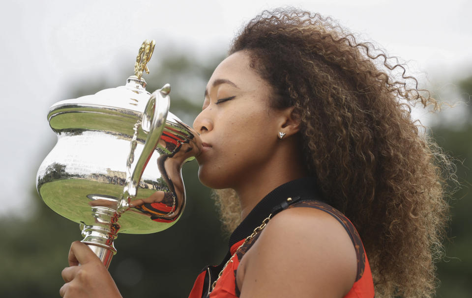 Japan's Naomi Osaka kisses the Daphne Akhurst Memorial Cup during a photo shoot at Government House the day after defeating United States Jennifer Brady in the women's singles final at the Australian Open tennis championship in Melbourne, Australia, Sunday, Feb. 21, 2021.(AP Photo/Hamish Blair)
