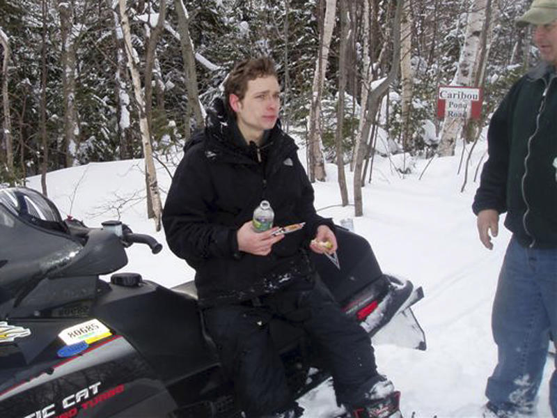 This photo released by the Maine Warden Service shows Nicholas Joy, 17, of Medford, Mass., sitting on a snowmobile Tuesday morning, March 5, 2013, after being found on a trail off the western side of Sugarloaf Mountain at Carrabassett Valley, Maine. Joy, who went missing Sunday during a family ski trip, survived two nights in the wild by building a snow cave for shelter, drinking water from a stream and walking toward the sound of snowmobiles during the day. (AP Photo/Maine Warden Service, Scott Thrasher)
