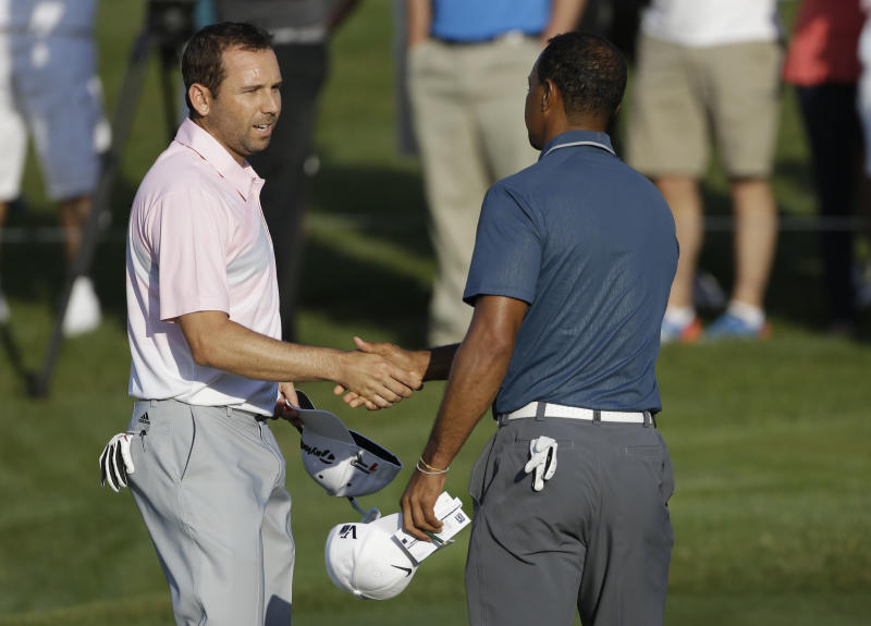 """In this photo made May 12, 2013, Sergio Garcia, of Spain, left, shakes hands with Tiger Woods at the end of the third round of The Players championship golf tournament at TPC Sawgrass in Ponte Vedra Beach, Fla. Garcia apologized to Woods on Wednesday, May 22, 3013, for saying he would have """"fried chicken"""" at dinner with his rival, a comment that Woods described as hurtful and inappropriate.  (AP Photo/Gerald Herbert)"""