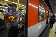 A devotee travels on the subway with his Saint Jude statue during the annual pilgrimage honoring Jude, the patron saint of lost causes, in Mexico City, Wednesday, Oct. 28, 2020. Thousands of Mexicans did not miss this year to mark St. Jude's feast day, but the pandemic caused Masses to be canceled and the rivers of people of other years outside the San Hipolito Catholic church were replaced by orderly lines of masked worshipers waiting their turn for a blessing. (AP Photo/Marco Ugarte)
